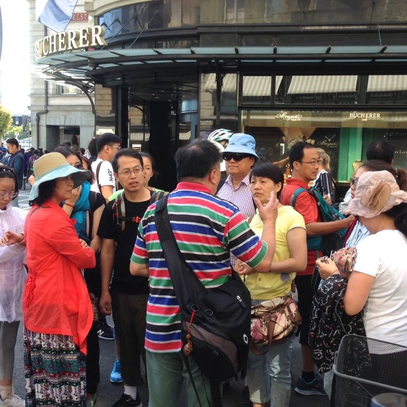 Der Reiseleiter gibt Anweisungen. Diese Gruppe am Schwanenplatz kommt aus Peking.