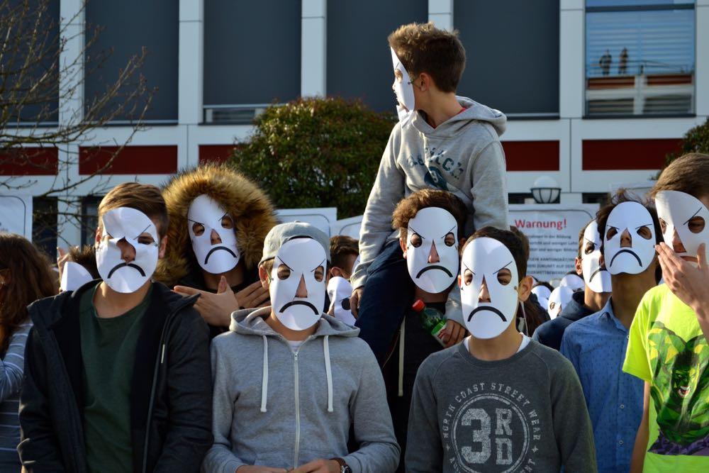 Die Maske soll dem Unmut der Lernenden Ausdruck verleihen.