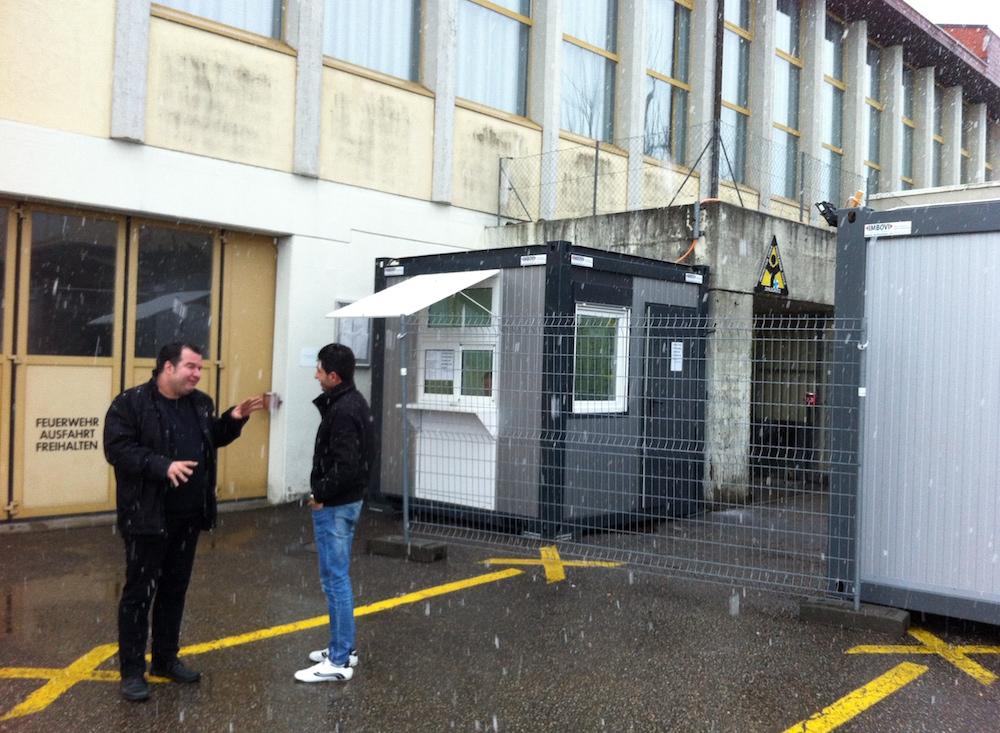 Unterkunftsleiter Marco Fellmann vor dem Asylzentrum im Gespräch mit einem Asylsuchenden.