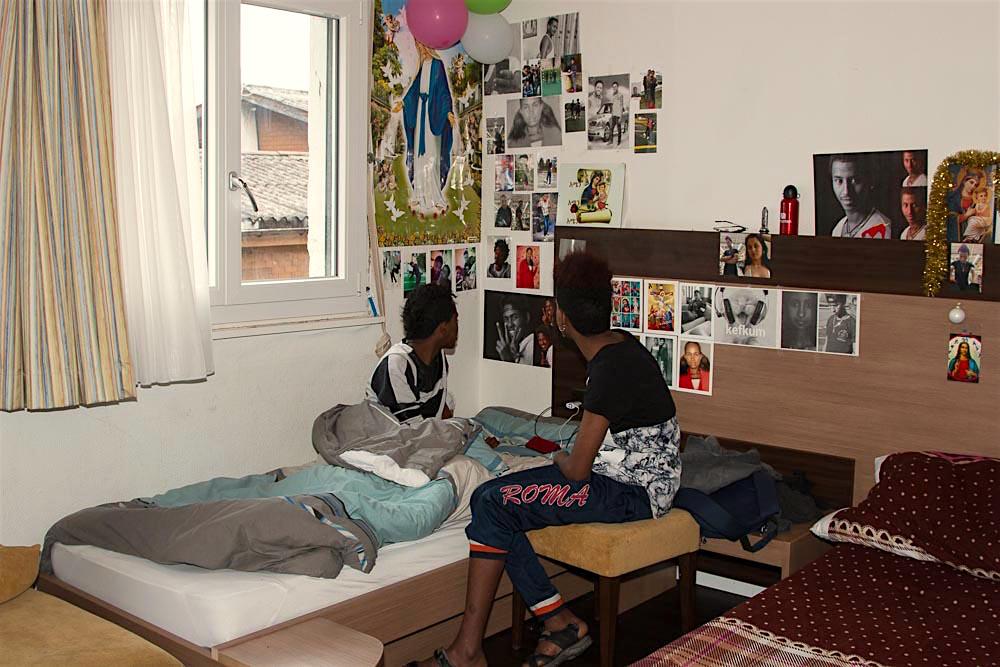 Zwei eritreeische UMA in ihrem Zimmer. An den Wänden befinden sich Erinnerungen an Eritrea und Symbole ihres Glaubens.