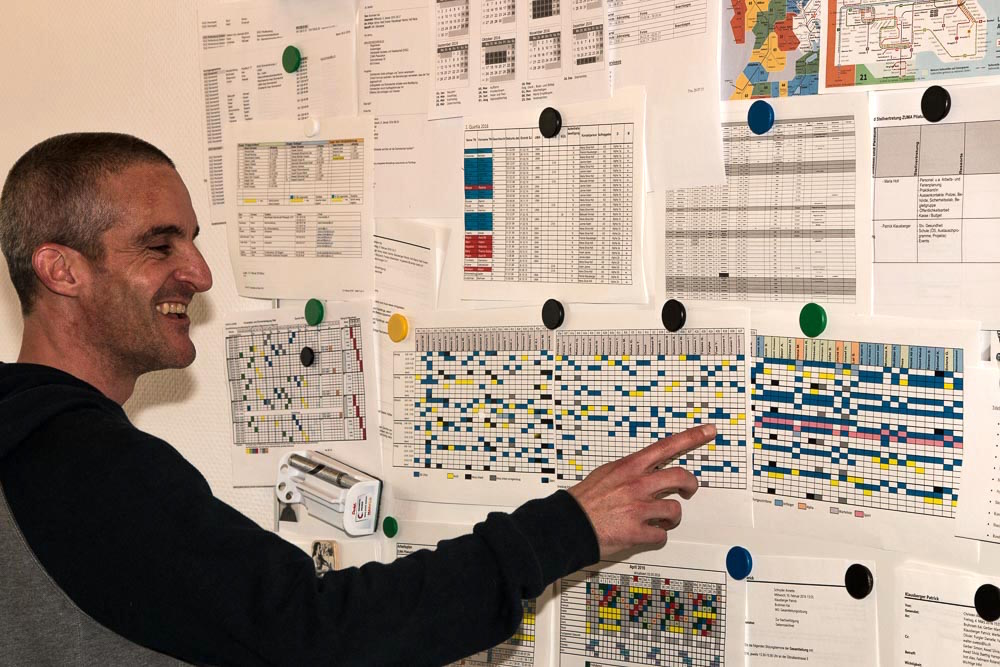 Patrick Klausberger zeigt auf den Plan. Jeder UMA hat seinen individuellen Tagesablauf.