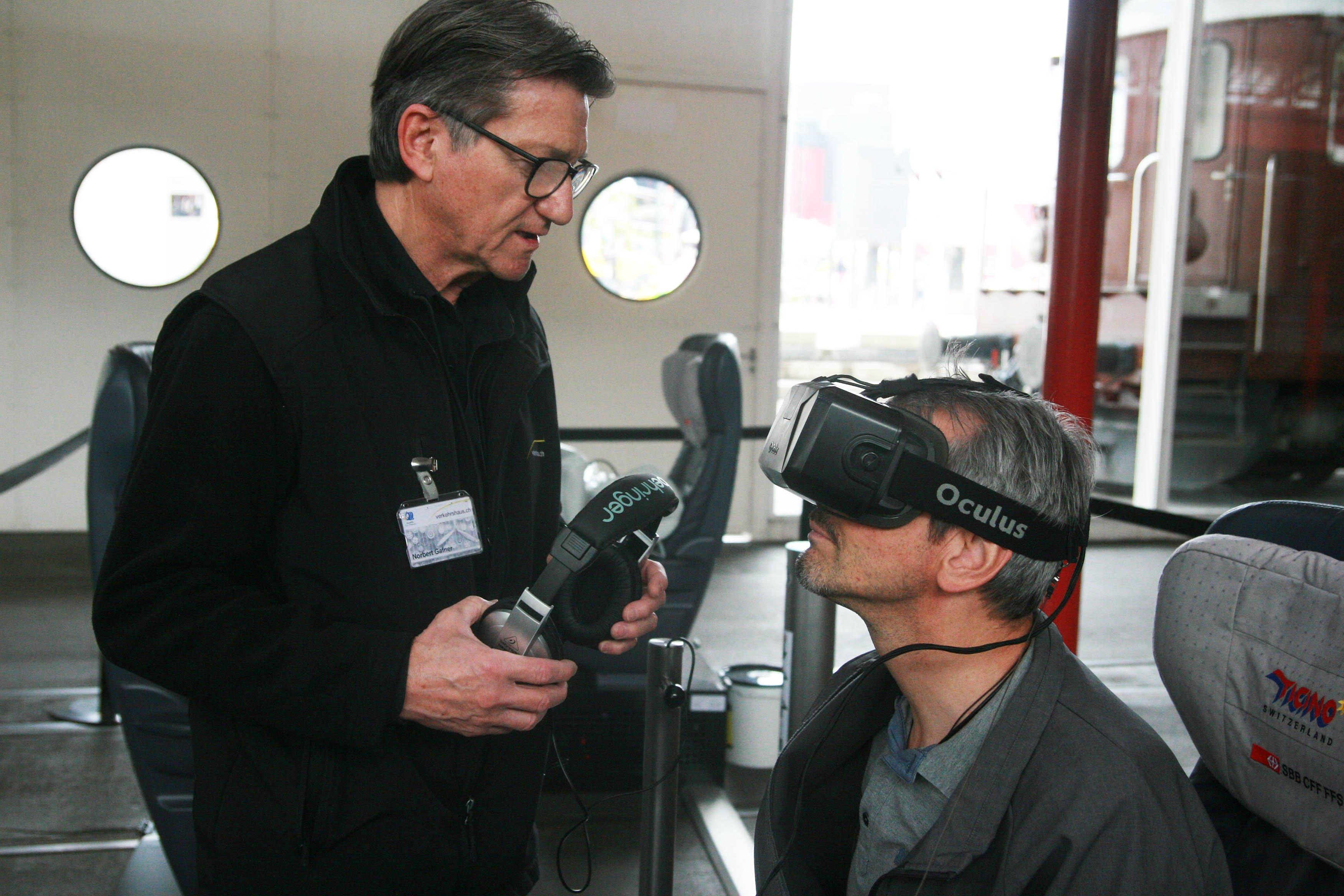 Marc Zihlmann (sitzend) lässt sich die 3D-Brille von einem Verkehrshaus-Mitarbeiter erklären.