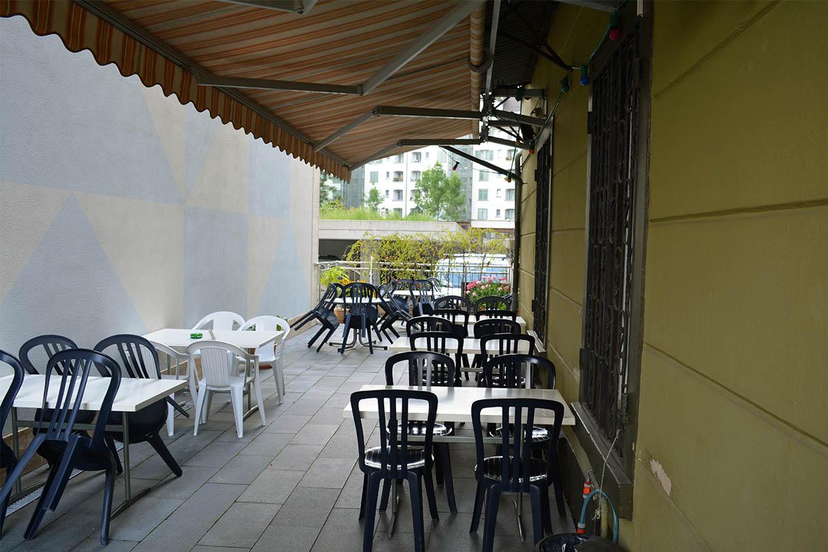 Der Gartensitzplatz, daneben die Hauswand des Hotel Fox.