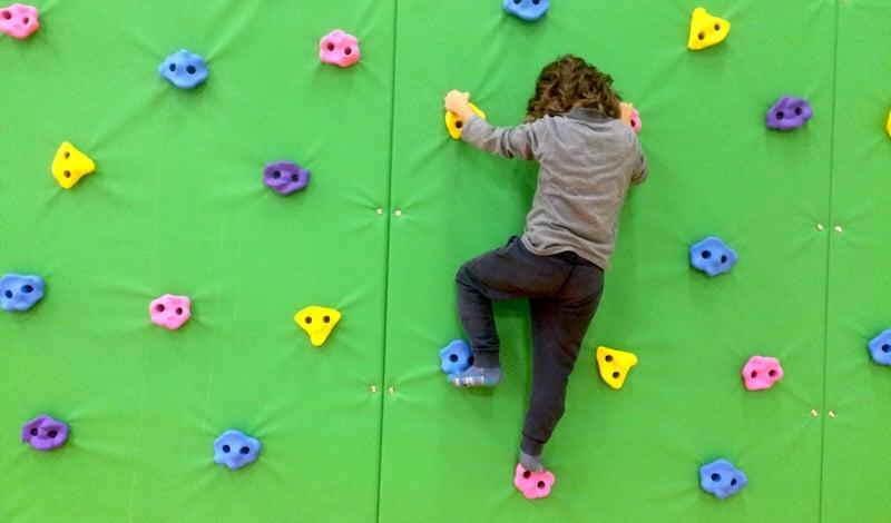 Nur nicht runterfallen. Ein Kind übt an der Kletterwand.