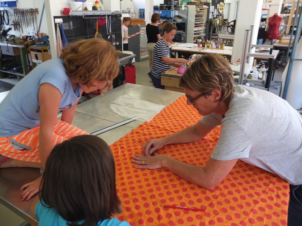 Erzinger hilft zwei Mädchen beim Zuschneiden des Stoffes. (Bild: Mirjam Oertli)
