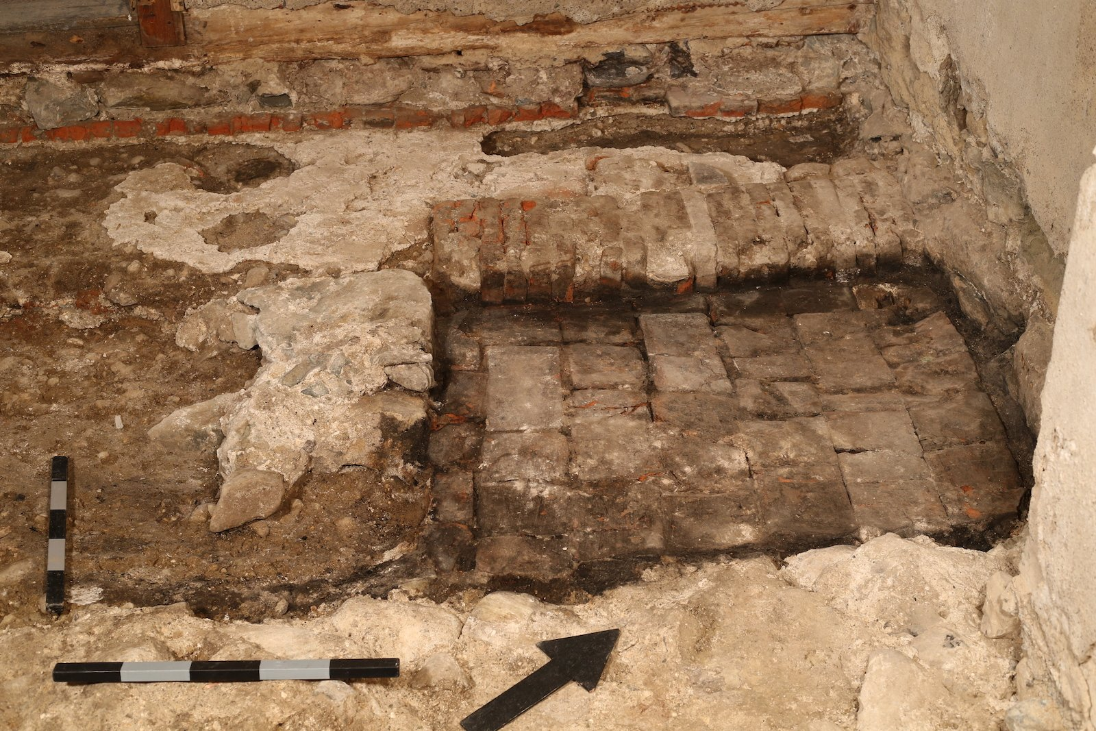 Im Sockelgeschoss der Brandruine, ehemals Kolinplatz 21, entdeckte man bei Ausgrabungen das Fundament eines mit Backsteinen gemauerten Backofens (Pfeil).