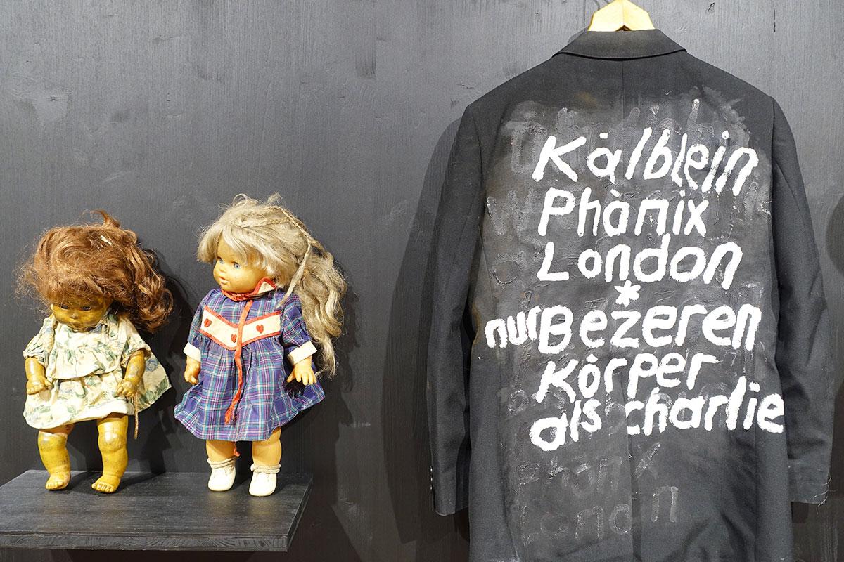 Auch Gegenstände sind in der Ausstellung zu sehen: ein Mantel und Puppen.