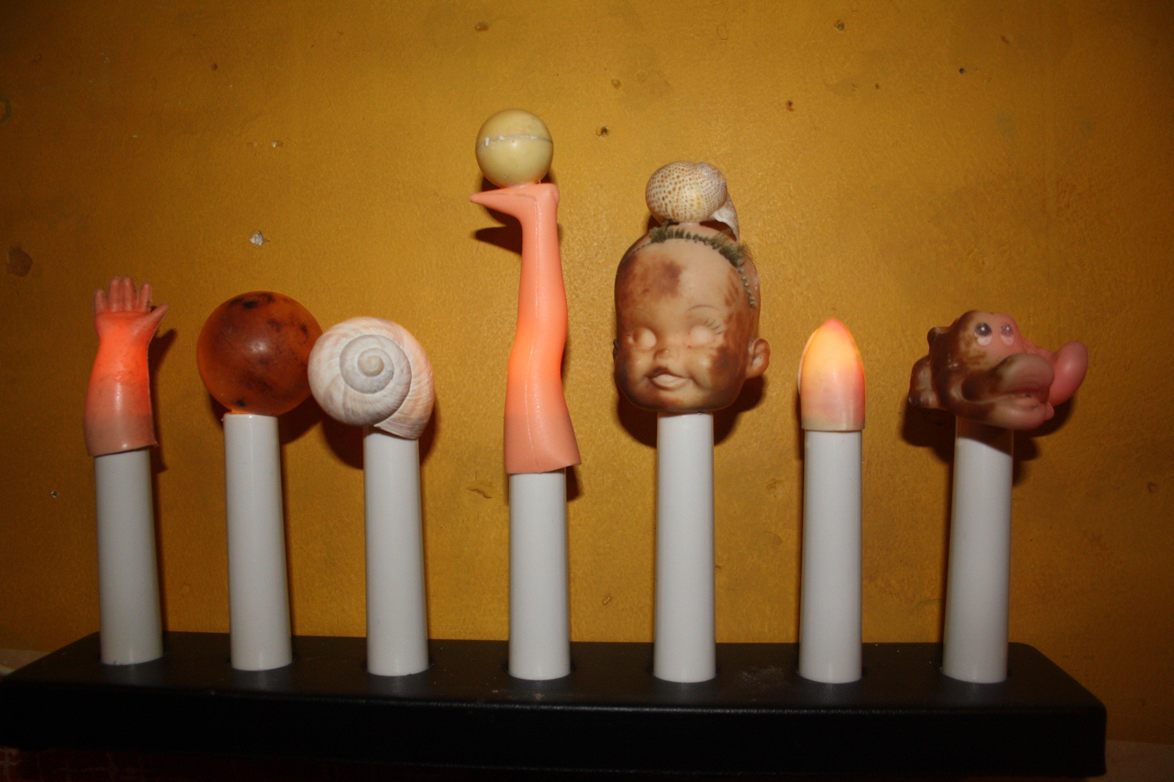 Kerzen mit Schneckenhaus und Puppenkopf statt Dochten.