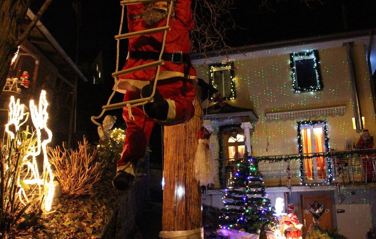 Ein Santa Claus klettert vor dem Haus herum.