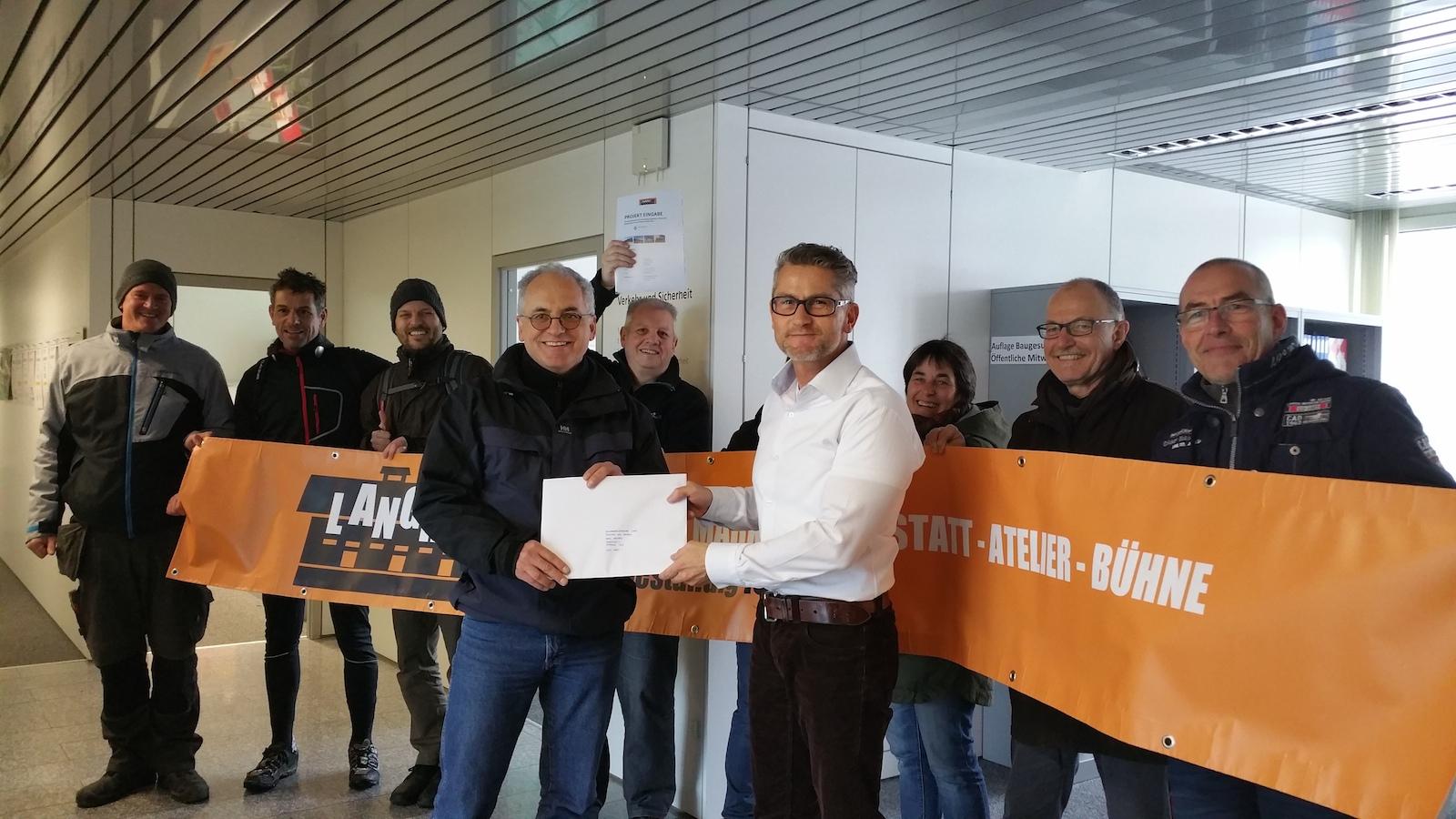 Einreichung im Mandelhof: Thomas Hauser (vorne links) übergibt Basil Stocker von der Einwohnergemeinde Cham das Langhuus-Konzept.