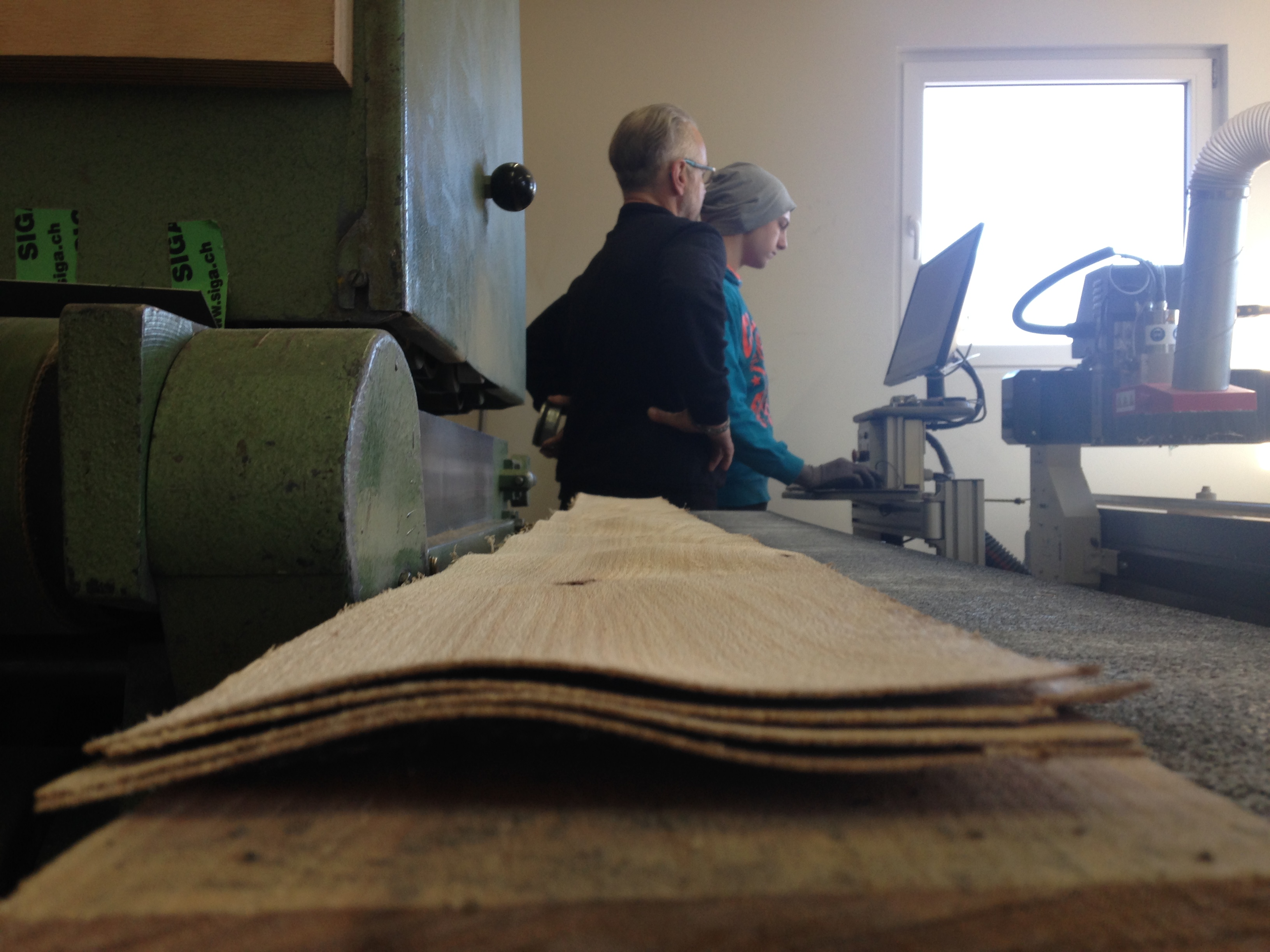 Zwei Holzbretter warten auf einen Durchgang in der Schleifmaschine. Im Hintergrund arbeiten René Unternährer und sein Praktikant. (Bild: zentralplus/bas)