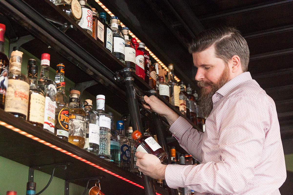 Gastgeber Tim Michel auf seiner neuen Bar-Leiter, die vom Partner seiner Mitarbeiterin hergestellt wurde.