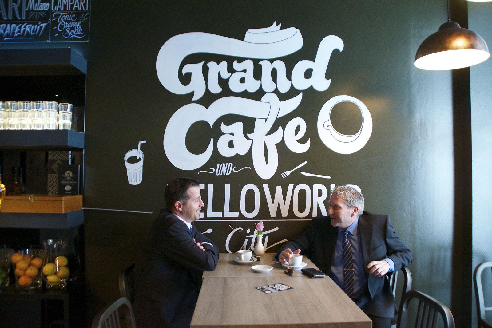 Zwei Zuger Geschäftsleute genehmigen sich einen Kaffee vor dem neuen Schriftzug.