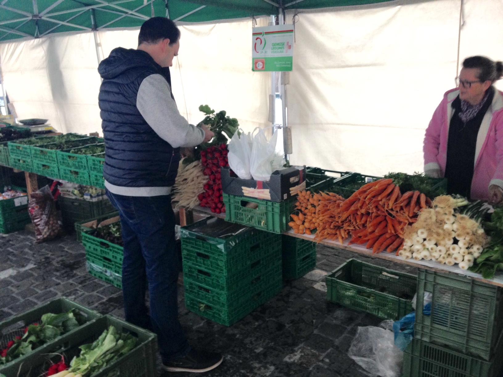Raphael Tuor inspiziert bei einem Gemüsehändler auf dem Luzerner Wochenmarkt die Pariser Karotten (Bild: bas/zentralplus).