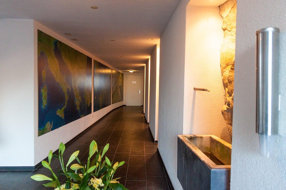 Der Eingangsbereich, rechts ein Becken aus der Wasser aus einer Quelle fliesst. Dieser spricht man Heilfähigkeiten zu.