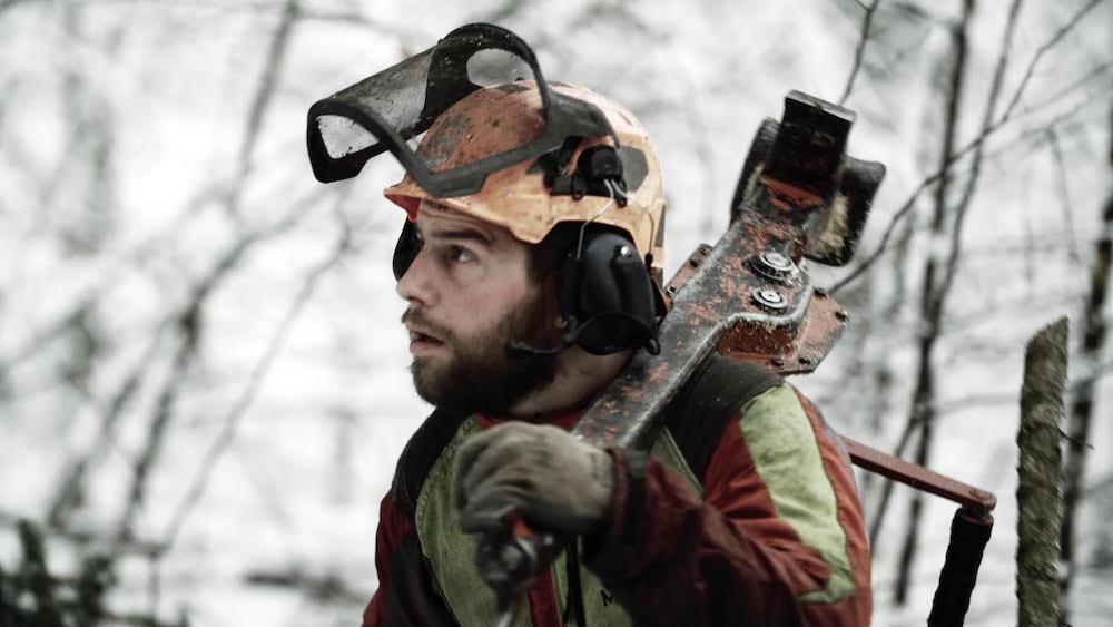 Ein Förster im Bergwald bei seiner Arbeit.