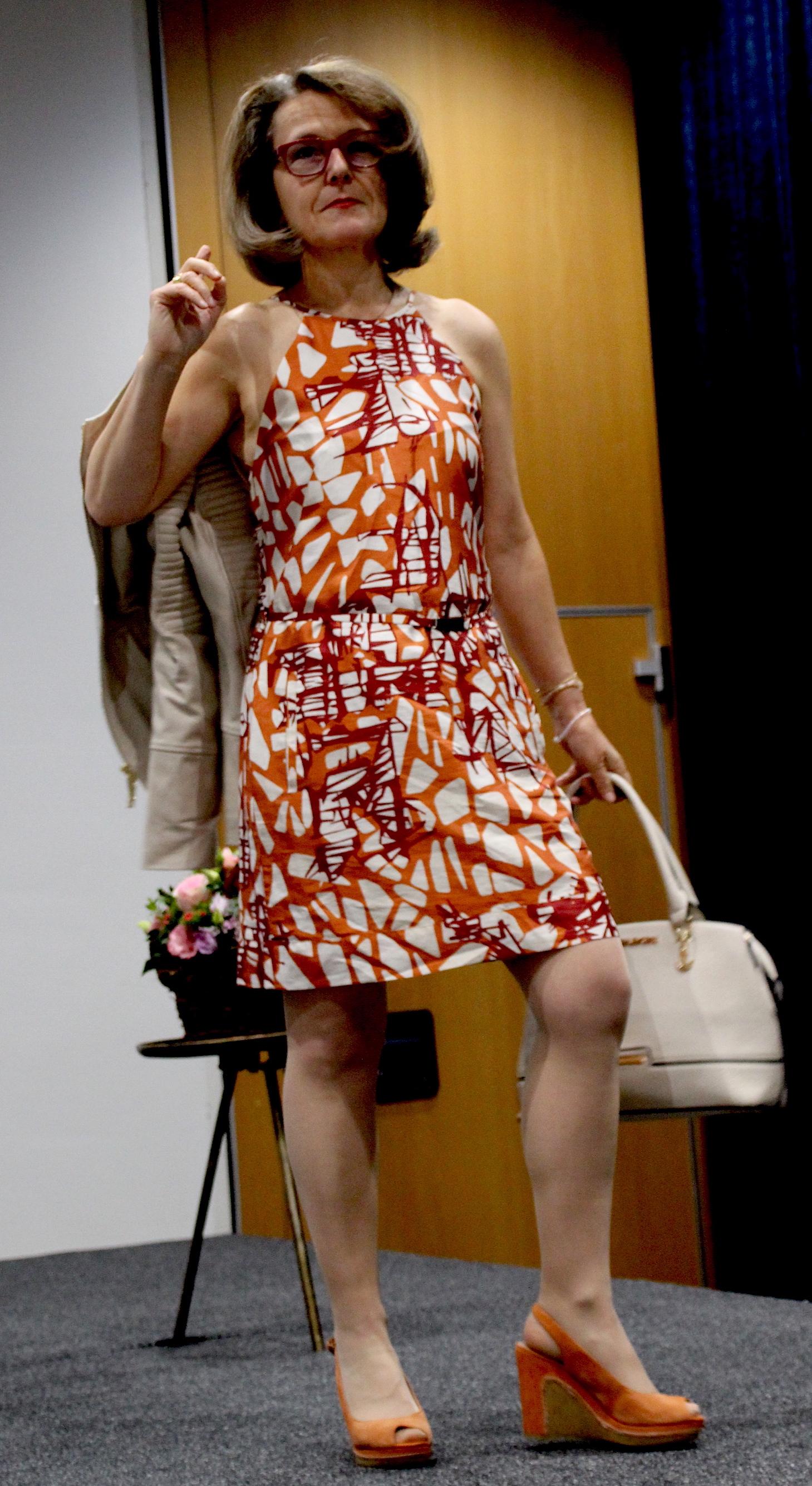 Gabriella trägt ein Kleid und eine Lederjacke von Hugo Boss und eine Handtasche von Michael Kors.