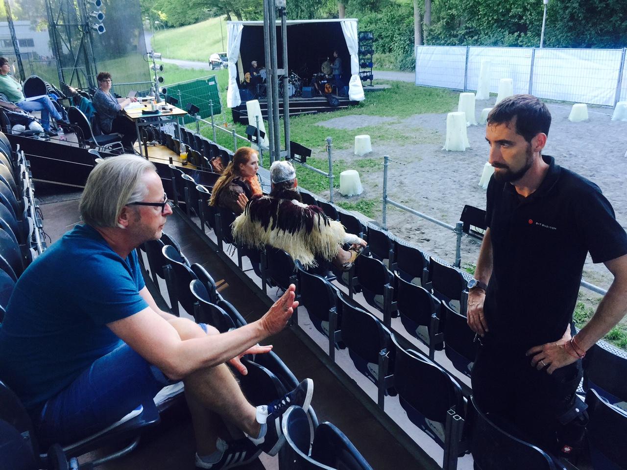 Um ihn dreht sich die ganze Produktion: Christoph Risi spricht mit einem Techniker, im Hintergrund übt die Band, rechts ein Ausschnitt der Bühne.