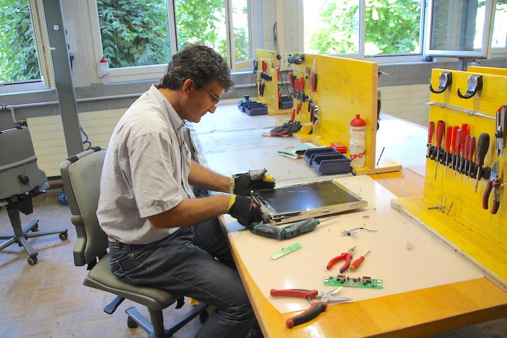 Kemal Bünül trennt einen alten Flachbildschirm in seine einzelnen Bestandteile auf.