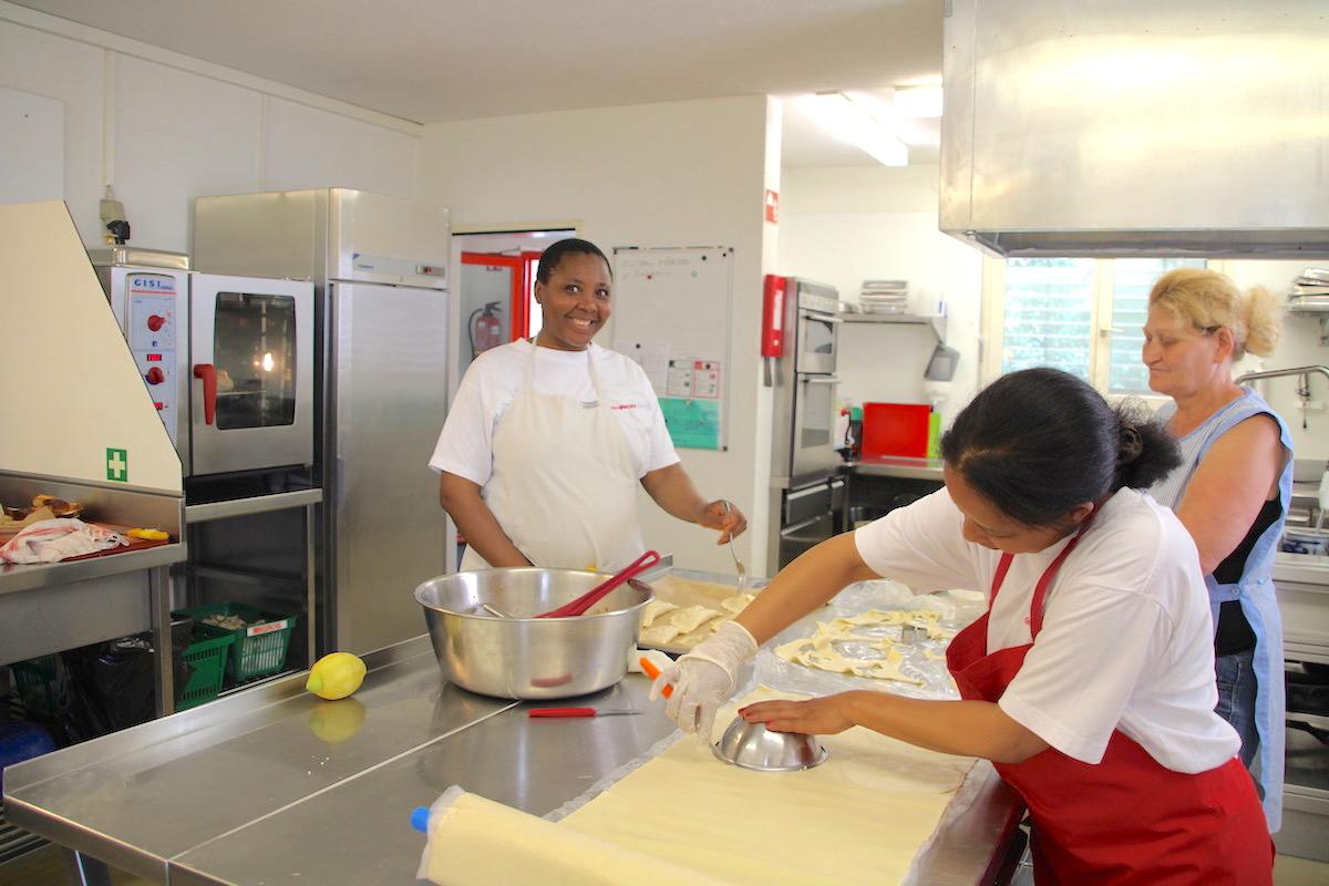 Elisé Soppi (links) bereitet mit ihren Kolleginnen das Mittagessen zu.