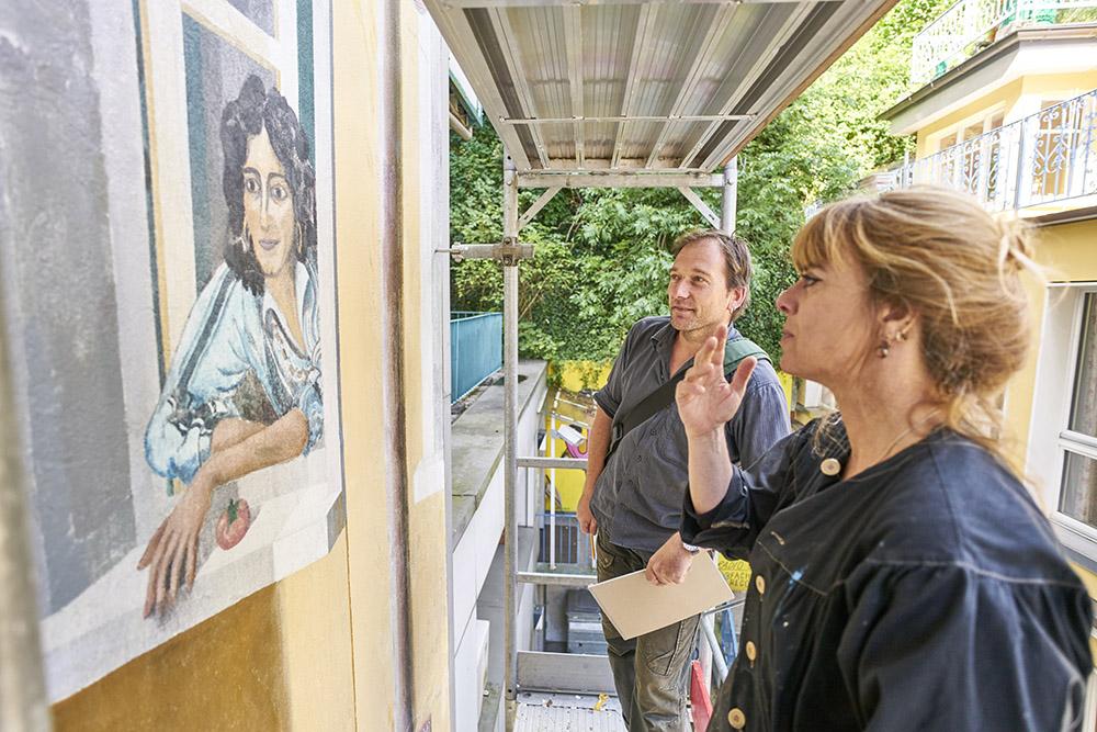 Marc Germann von Quartierverein Hochwacht sieht sich mit Sylvie Meylan, Dekorationsmalerin, das Bild genau an.