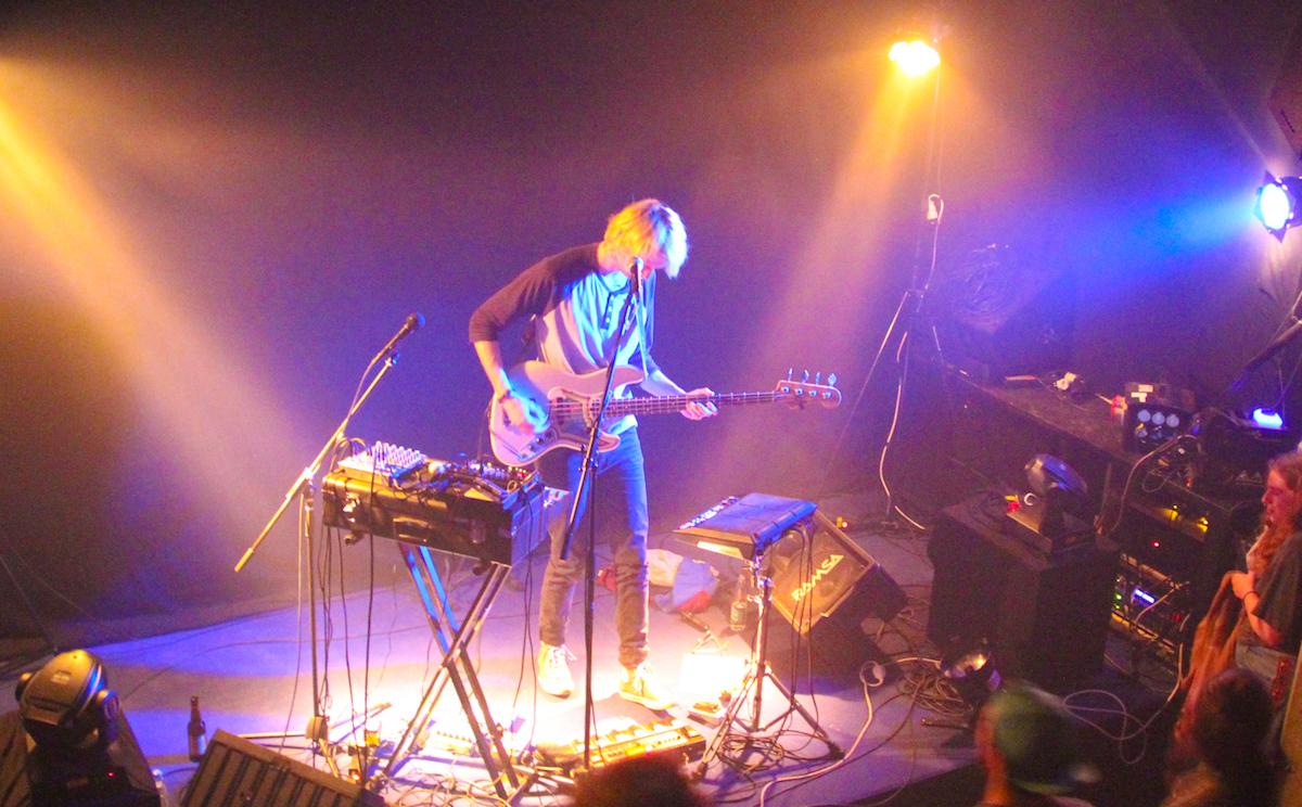 Steht zwischen Drum Machine und Synthesizer mit seiner Bassgitarre: Nick Furrer.