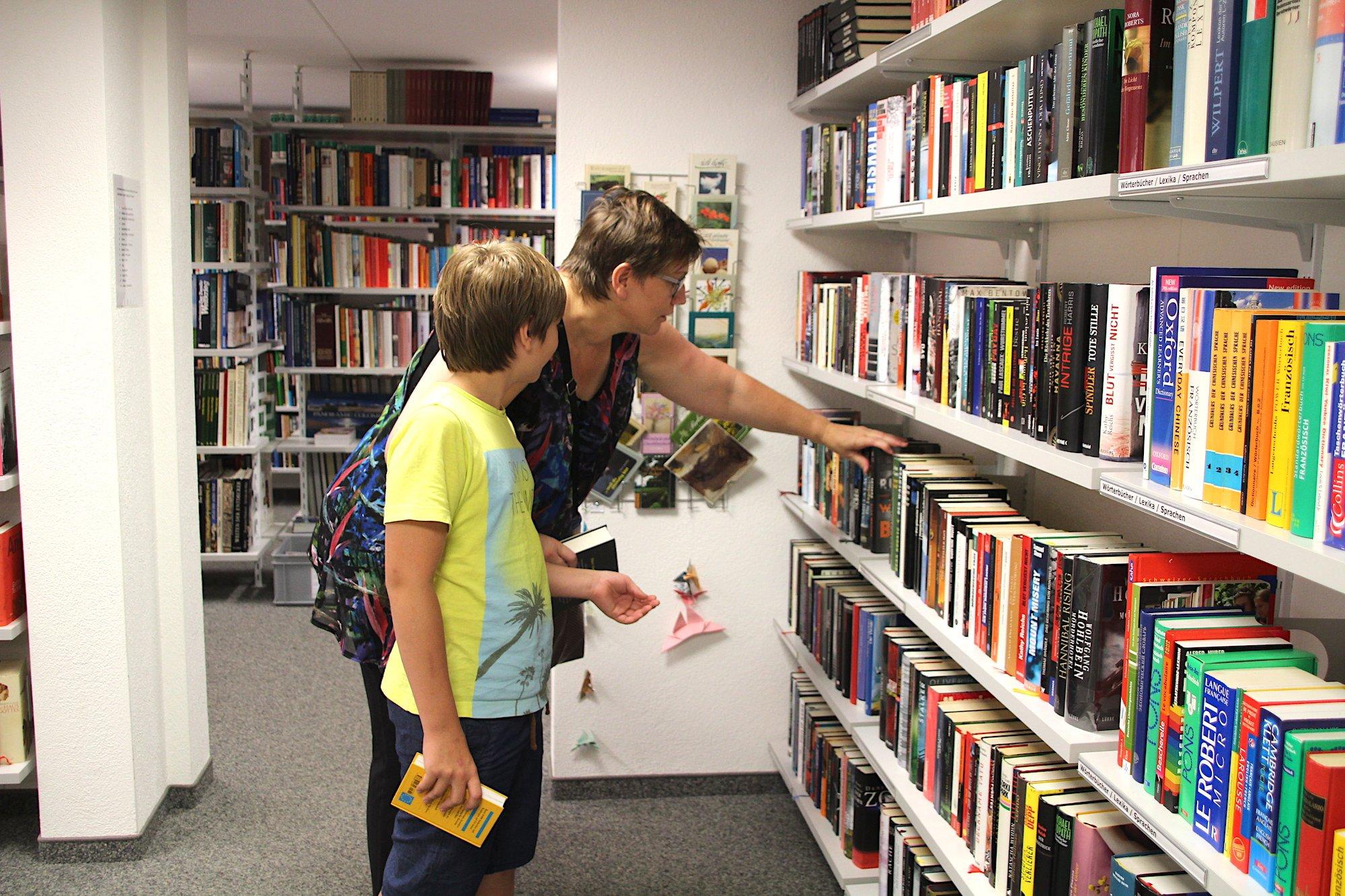 Karin Franzen und ihr Sohn Nils suchen sich Bücher aus in der Gratis-Bibliothek der Halle 44 in Baar. Bis zu zehn Bände darf man mit nach Hause nehmen.