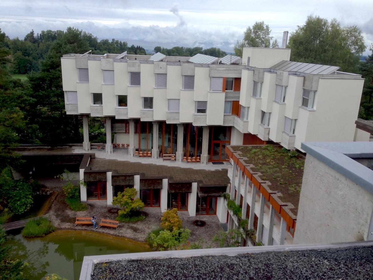 Das Lassalle-Haus ist U-förmig gebaut. In der Mitte liegt ein grüner Park mit Teich.