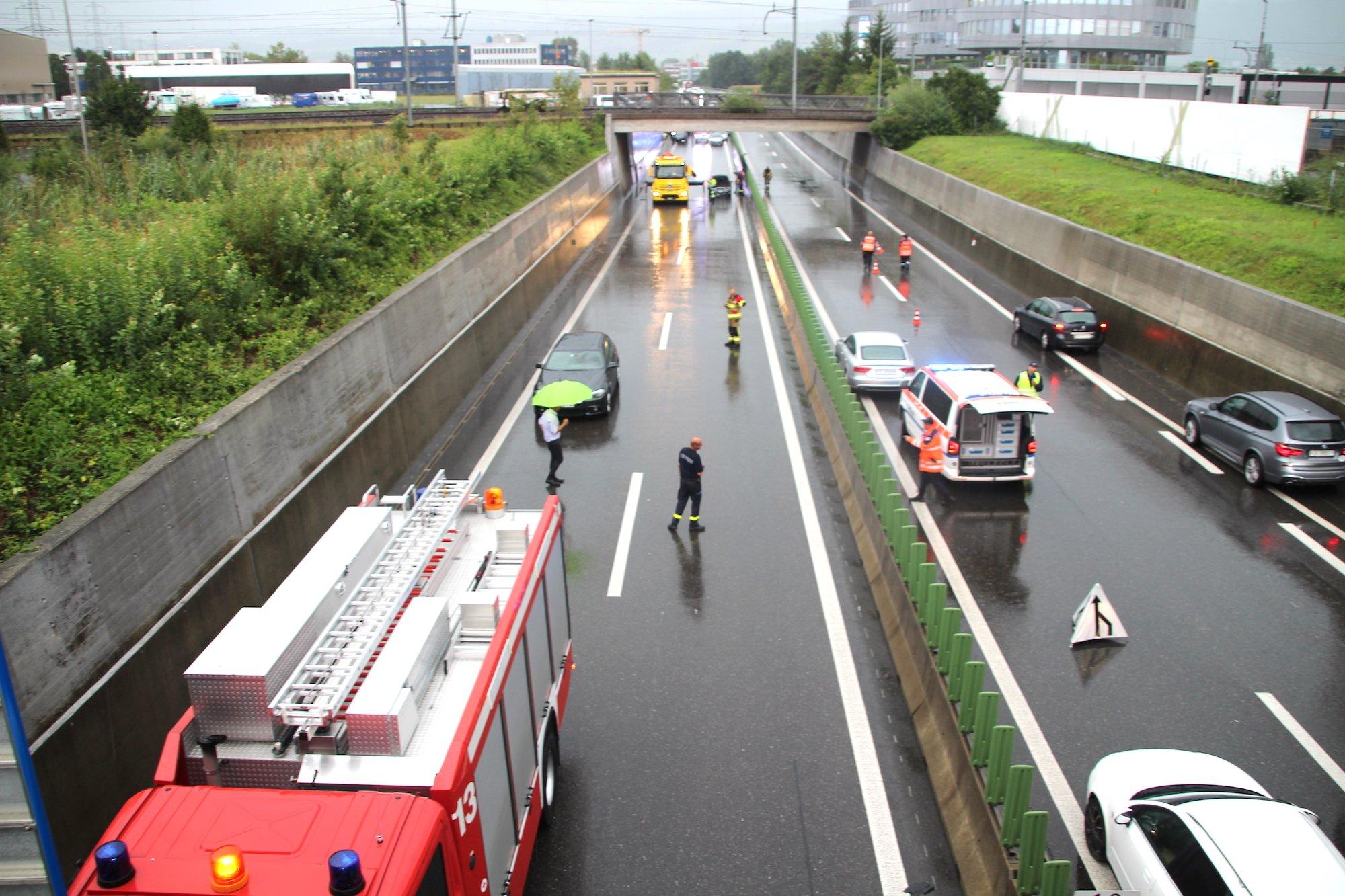 Die Feuerwehr und die Zuger Polizei versuchen dem Hochwasser auf der gesperrten Autobahn Herr zu werden.