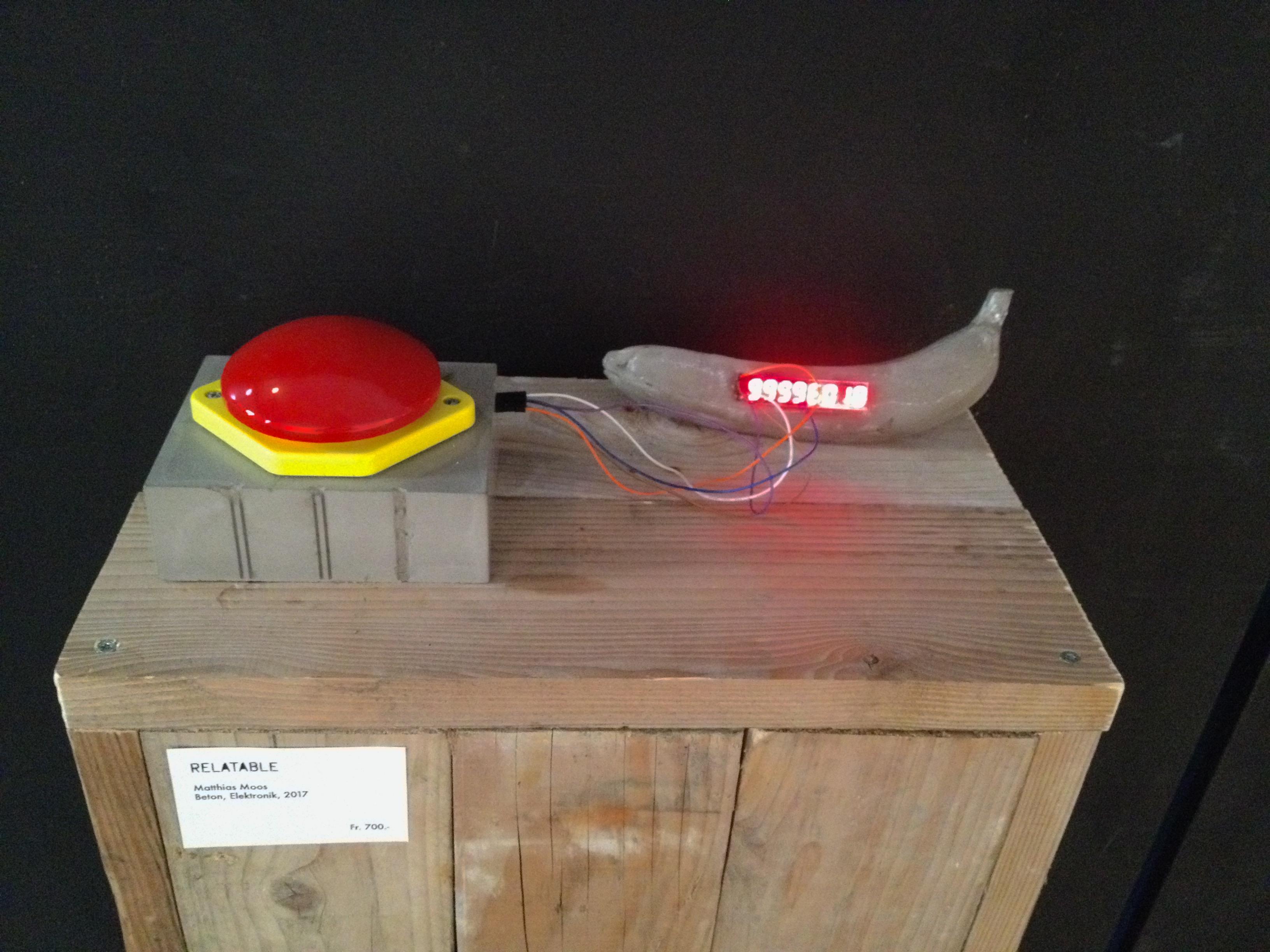 Einer der roten Knöpfe aus der Ausstellung, verbunden mit einer Bananen-Bombe.
