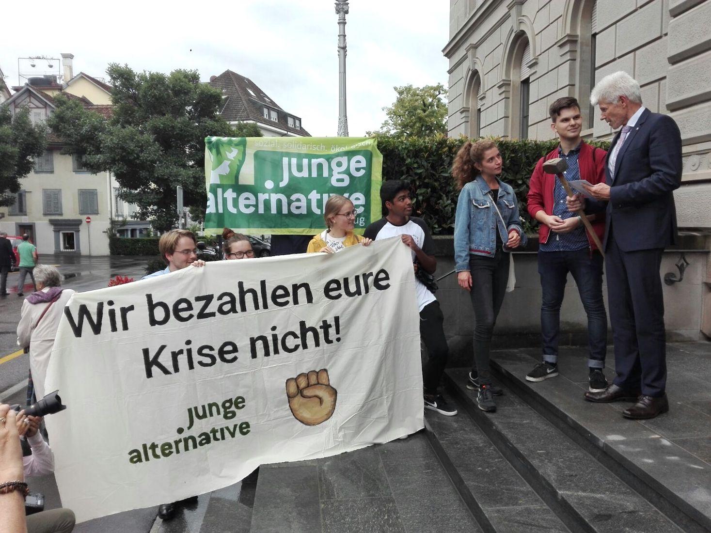 Gegen Sparpolitik: Junge Alternative übergeben dem Zuger Kantonsratspräsident Daniel Thomas Burch (FDP) einen Protestbrief und einen «Sparhammer».