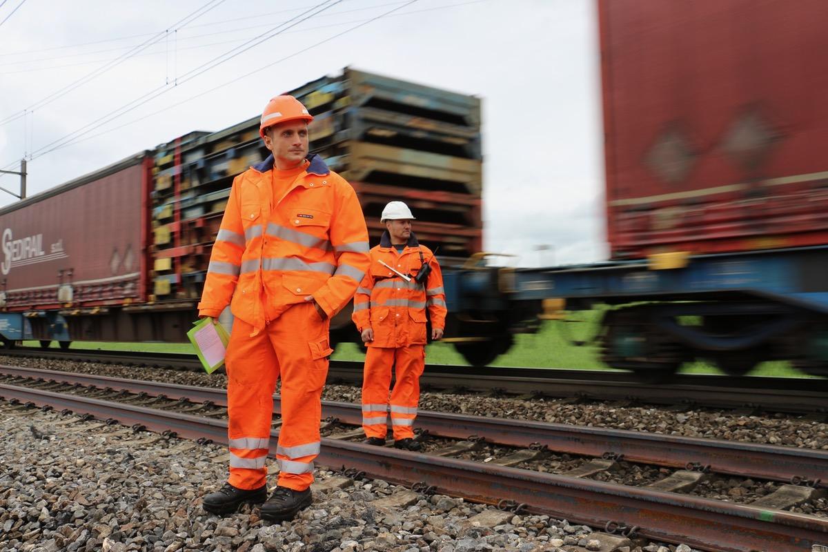 Arbeiten am offenen Herzen quasi: Bauarbeiter arbeiten am Gleis, während daneben der Güterzug vorbeirattert.