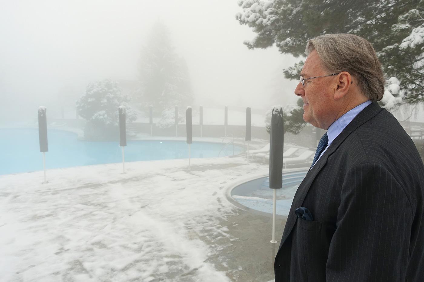 Resort-Chef Bruno H. Schöpfer blickt über die Gartenanlage und das historische nierenförmige Pool.