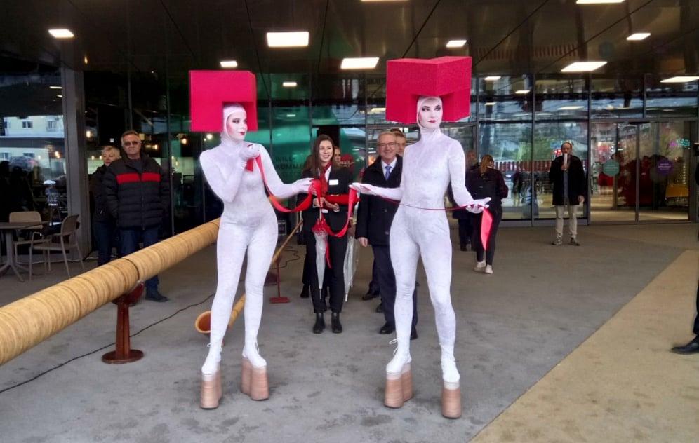 Zwei kostümierte Frauen halten ein rotes Band. Im Hintergrund Regierungsrat Robert Küng, der dieses gleich durchschneiden wird.