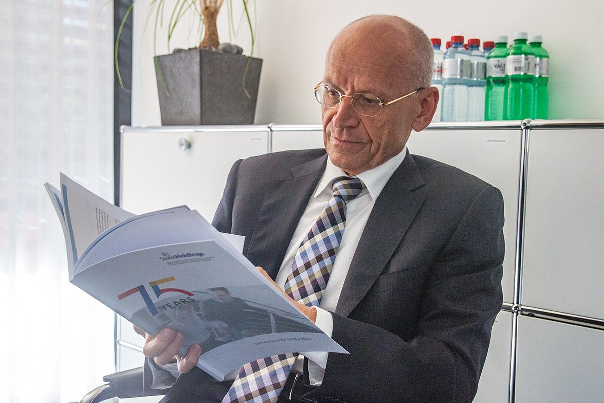 Swissholdings-Präsident Karl Hofstetter blättert durch die Jubiläumsbroschüre des Verbandes.