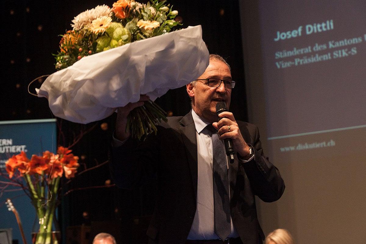 Guy Parmelin empfängt einen Blumenstrauss nach seinem Auftritt.