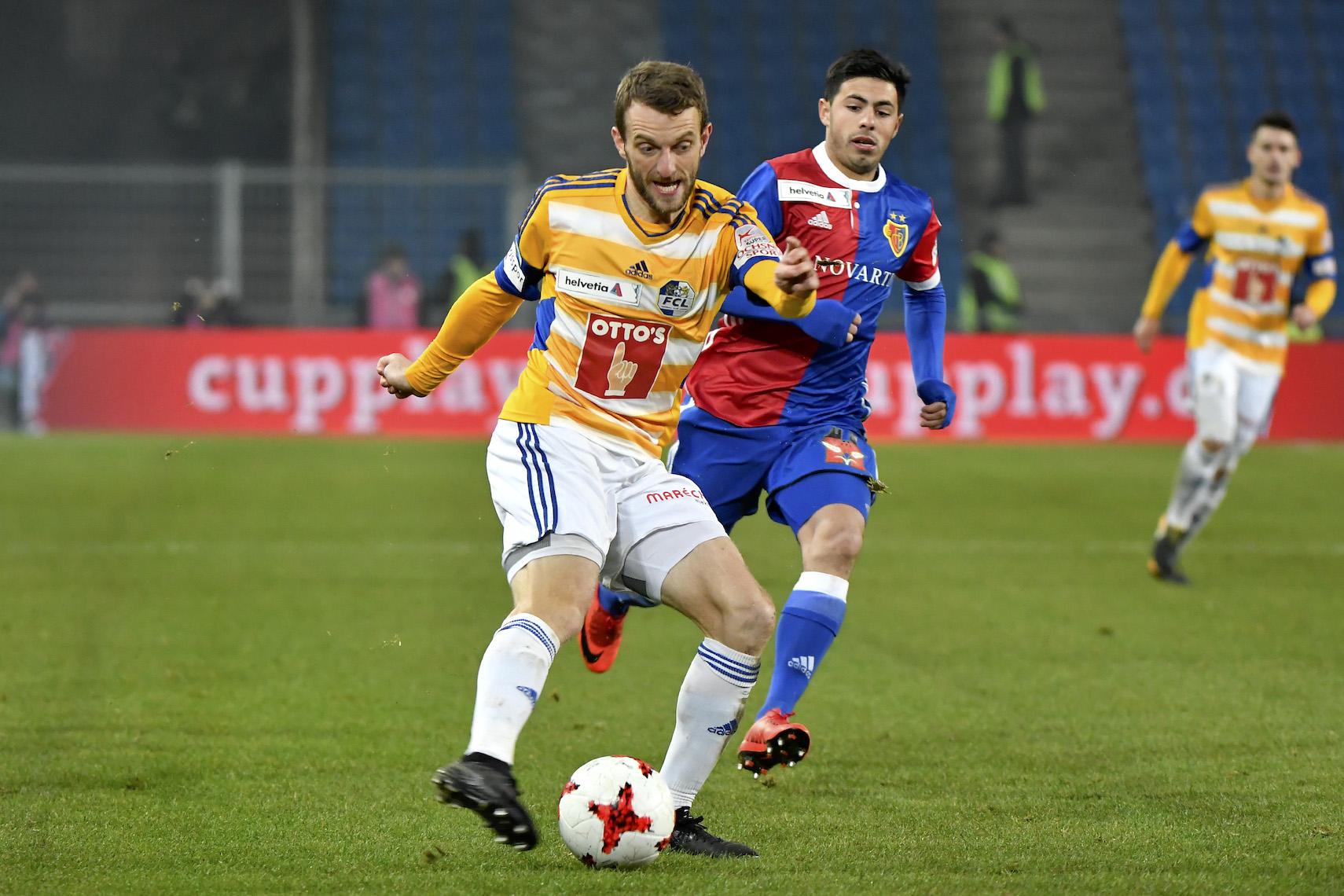 Christian Schneuwly bleibt am Ball: Hier gegen Basels Blas Riveros im Cup.
