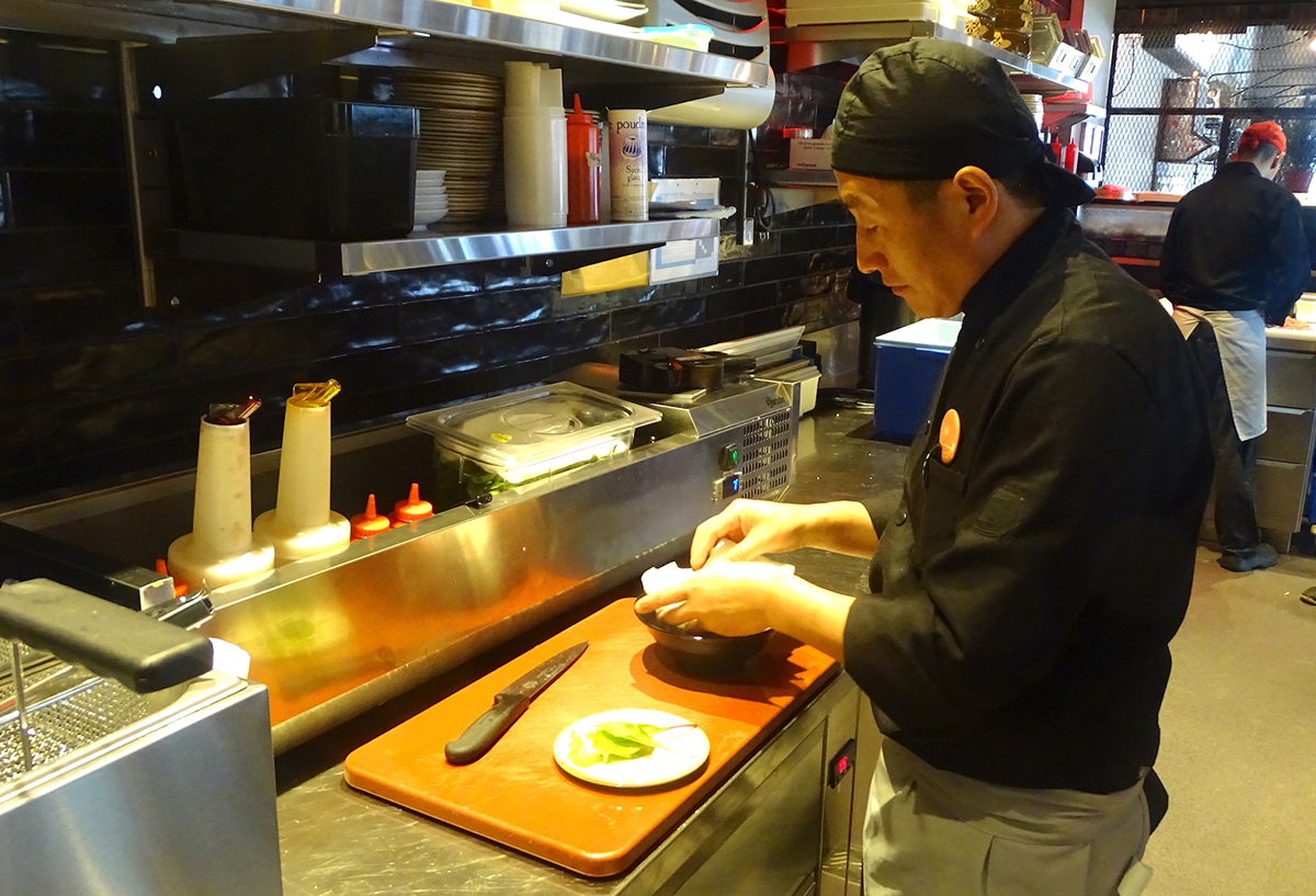 Ein Koch im «Nooch Asian Kitchen» bei der Zubereitung der Heuschrecken.