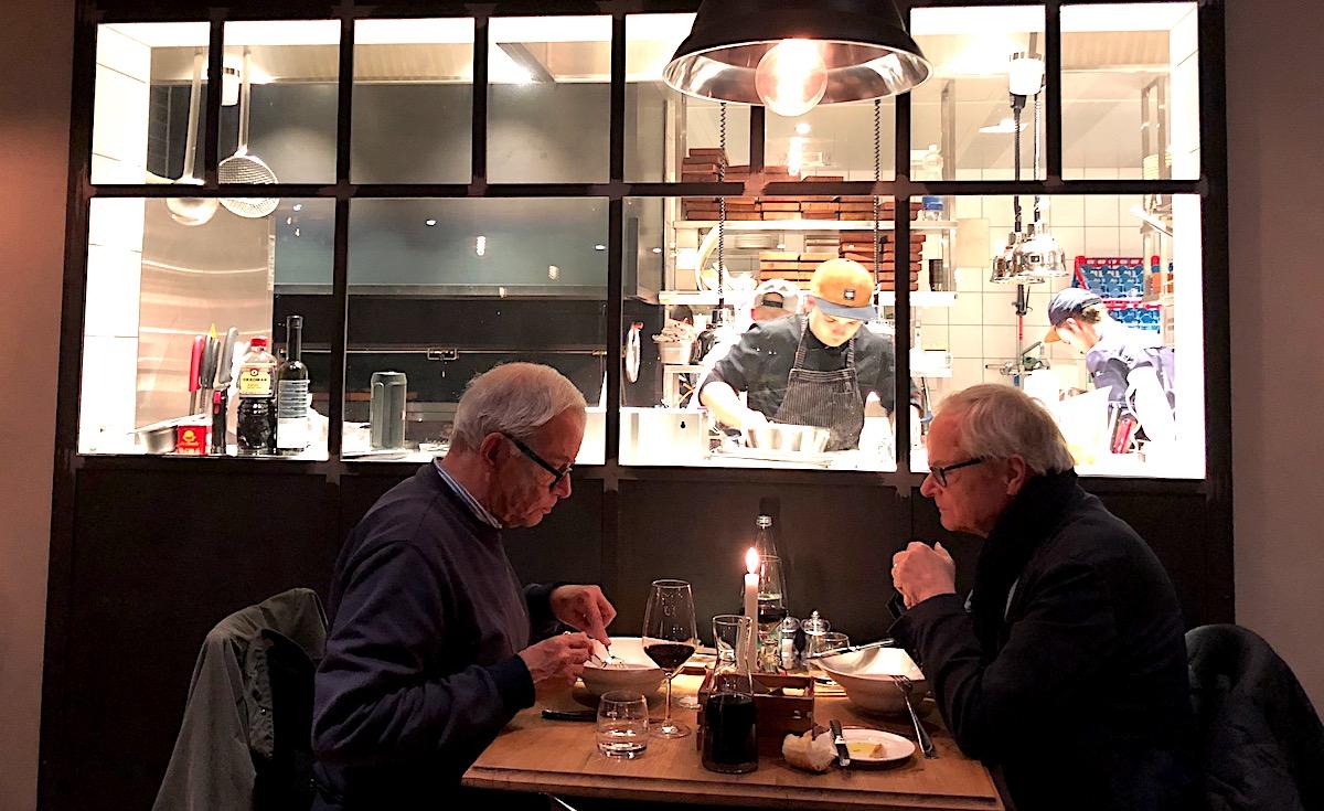 Ein Bild wie von Edward Hopper: über dem Essen meditierende Gäste, im Hintergrund die Küche.