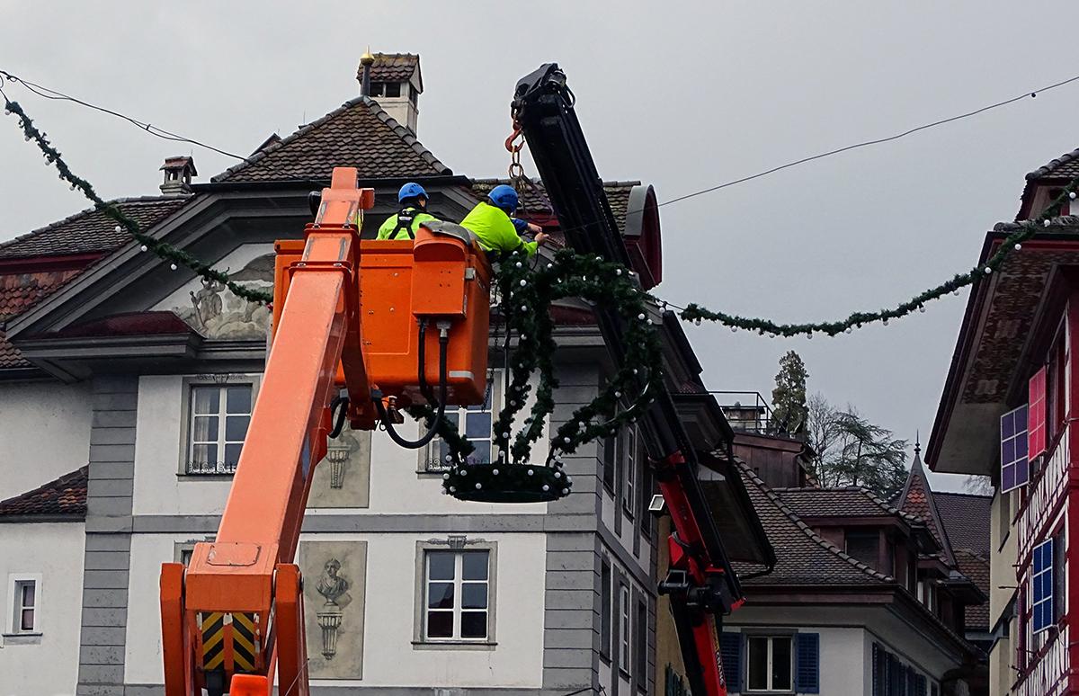 Mitarbeiter der ewl bei der Demontage der Krone über der Reussbrücke.