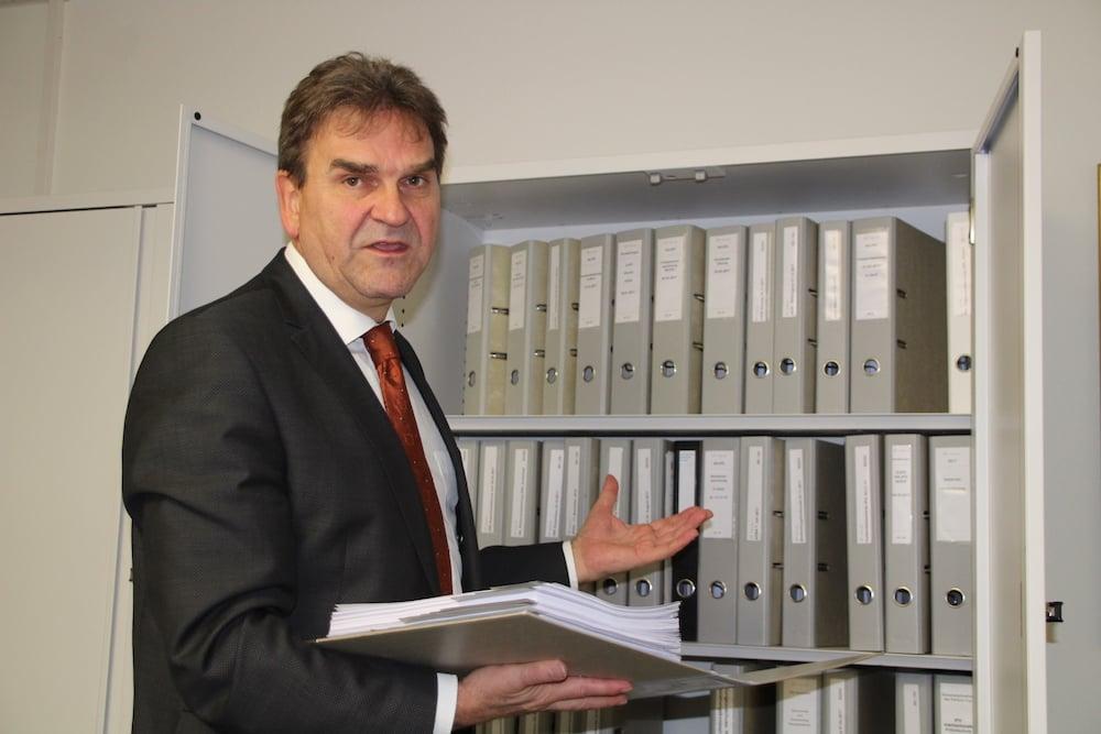 Zugs Sicherheitsdirektor Beat Villiger demonstriert am Aktenschrank in seinem Büro, wie stark die Zuger Polizei an interkantonalen und bundesweiten Projekten mitarbeitet.