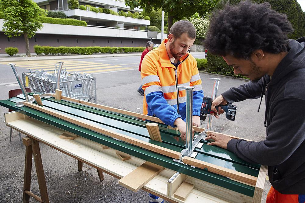 Benedikt Bucher, Leiter ReFit vom Strasseninspektorat Luzern montiert zusammen mit einem Mitarbeiter eine Sitzbank.