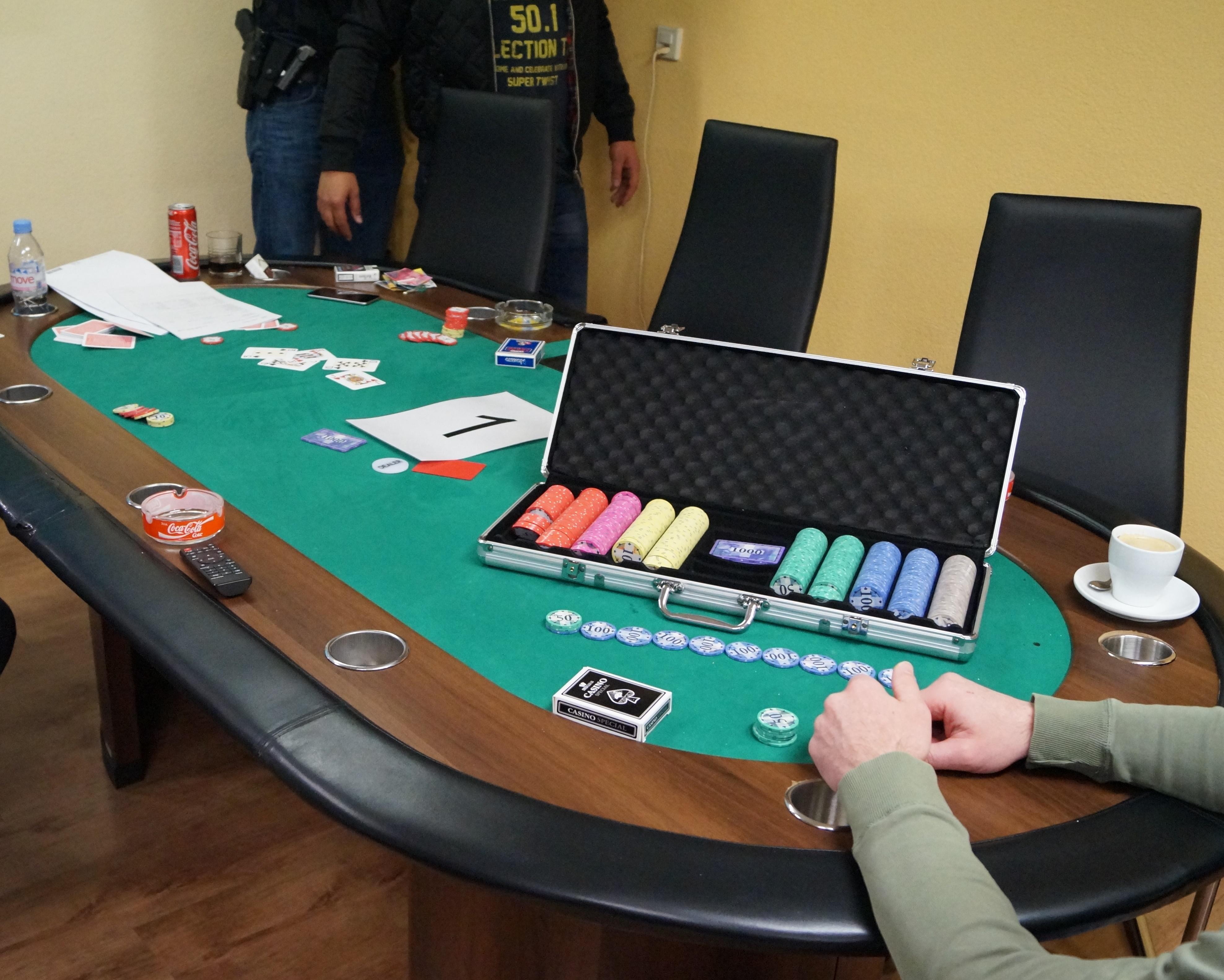 Szene einer Razzia in Zug: Männer sitzen am Tisch und spielen illegale Glücksspiele.