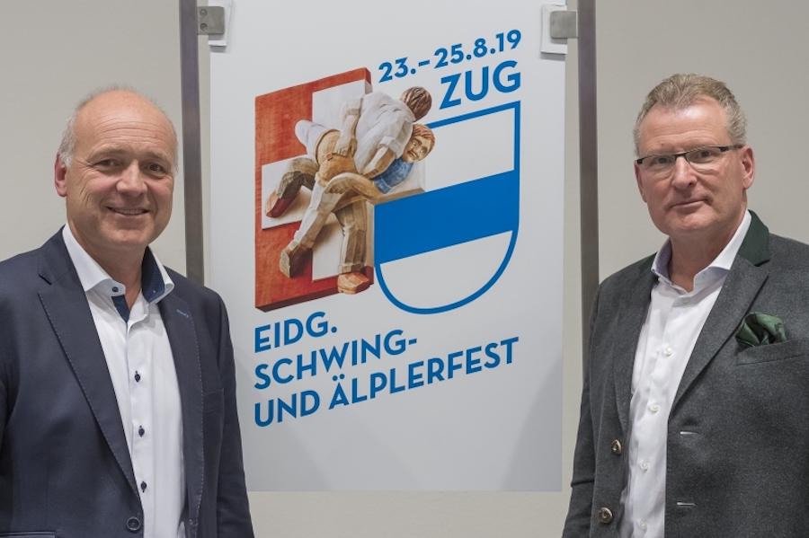 OK-Präsident Heinz Tännler (rechts) mit dem Logo und einem Sponsor des Fests.