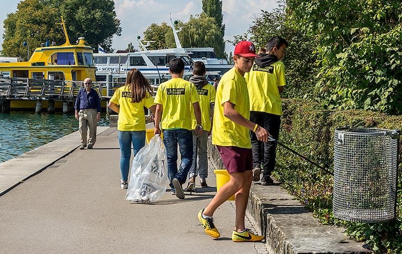 Clean Up Day Zug, Jugendliche sammeln in der ganzen Stadt Litteringabfaelle. Urs Raschle hilft ihnen dabei beim Fundbuero fuer gefundenen Abfall. Hier ein Team beim Sammeln am See