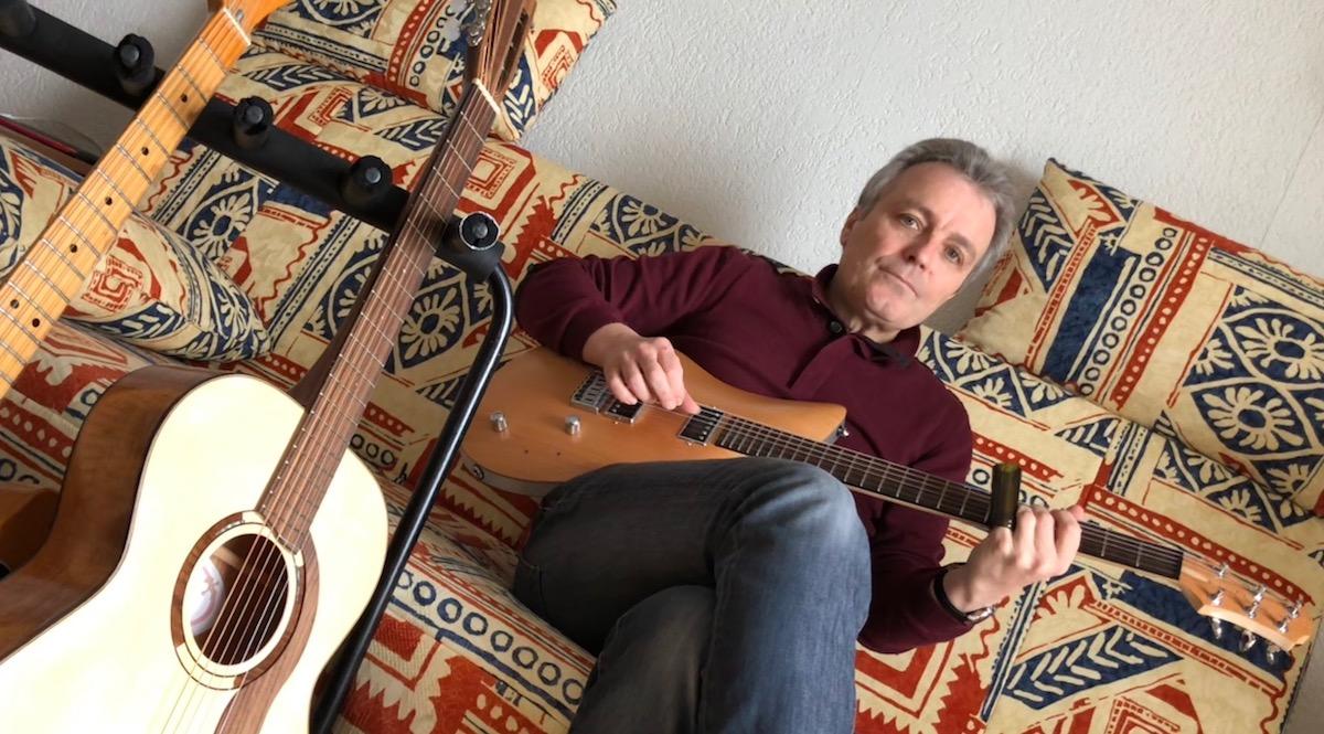 Richard Koechli zu Hause auf seinem Sofa, in der Hand eine Luzerner Relish-Gitarre.