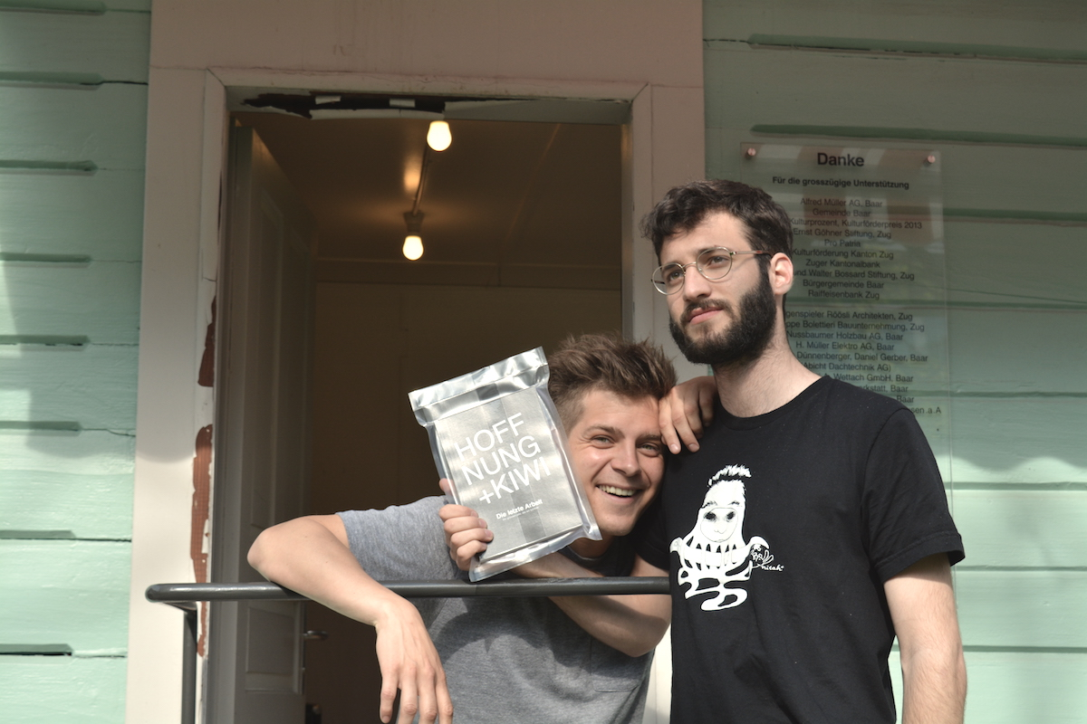 Michel Kiwic (links) und Severin Hofer, auch bekannt als Künstlerduo Hoffnung+Kiwi beim Kunstkiosk in Baar. In den Händen ihr erstes literarisches Werk.