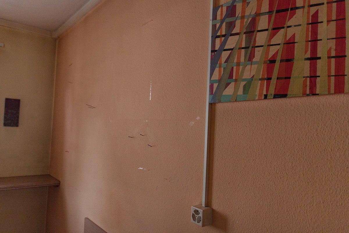 Dicke Nägel säumen die Zimmerwand und es riecht streng nach Zigaretten.