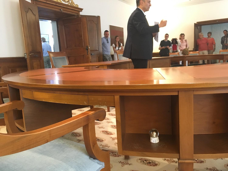 Guido Grafs kleiner Glücksbringer: sie kleine Schneekugel an seinem Sitzplatz im Regierungszimmer. Im Hintergrund erklärt Graf den Leuten die Arbeit der Regierung.