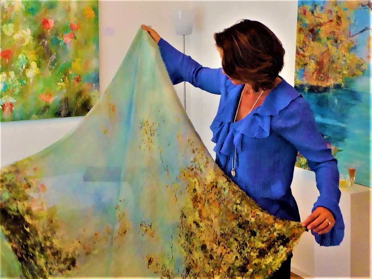 Claudia Limacher demonstriert ihre Malkunst auf kunstvollen Schals.